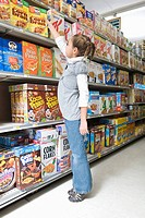 Young girl reaching for ceral product in supermarket aisle