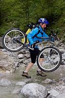 Cyclist crossing a stream, Styria, Austria