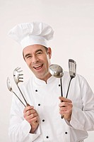 Cook laughing, holding cooking utensils