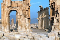 The archeological site of the greco-roman ruins of the city of Palmyra with a big arch leading to a long, ancient drive way made of stones, at blue sk...