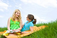 Two smiling girls on a blanket in the grass