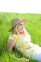 Portrait of a smiling blond girl wearing a sun hat while lying on a meadow