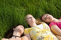 Three girls sleeping in the grass