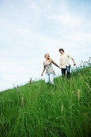 Young couple in love, holding hands while running in a meadow