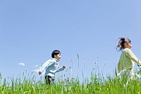 Japan, Tokyo Prefecture, Children running in meadow, side view