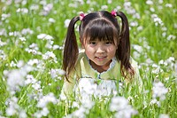 Japan, Tokyo Prefecture, Girl sitting in meadow, smiling, portrait