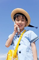 Japan, Tokyo Prefecture, Boy wearing straw hat using mobile phone, portrait