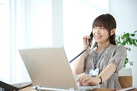 Japan, Osaka Prefecture, Businesswoman using laptop, on the phone