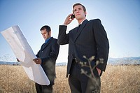 2 men with plans in field, one on phone