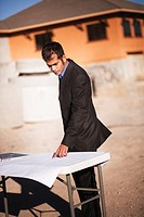 Man examining plans on worksite