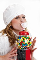 Young woman chewing gum, next to a gumball machine