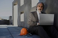 Man sitting on sidewalk using laptop, hard hat set at side, unfinished building in background