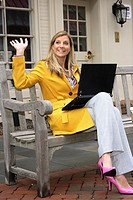 Woman waving outdoor with a laptop