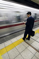 A businessman waits on a subway platform Tokyo Japan