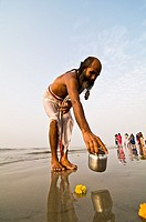 A Hindu pilgrim performing a puja ceremony during the Gangasagar mela / festival which takes place every January on gangasagar island.