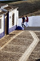 Young couple walking through a town in Spain. Campo de Criptana, Spain