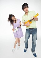 Young man and woman playing the ukulele