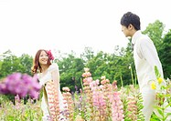 Bridal couple walking through a field of flowers
