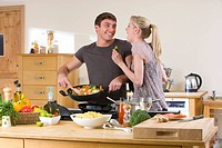 Couple cooking fresh vegetables in kitchen