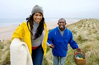 Happy couple on beach with picnic basket and blanket