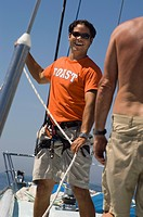 Smiling Sailor Working Ropes on Yacht portrait
