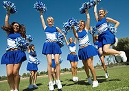 Group of Cheerleaders rising pom-poms jumping on football field (thumbnail)