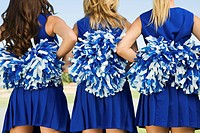 Cheerleaders holding pom_poms rear view mid section close_up