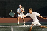 Tennis Player stretching Swinging at Ball near tennis net doubles partner standing behind (thumbnail)
