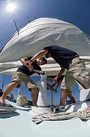 Sailors operating windlass on yacht low angle view wide angle lens (thumbnail)