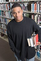 Young man holding books underarm in Library (thumbnail)