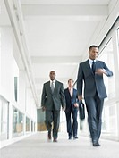 Businessmen walking down corridor low angle view