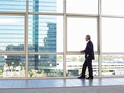 Businessman looking out of office window (thumbnail)