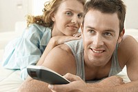 Couple on bed relaxing together man holding remote control (thumbnail)