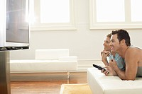 Couple lying on bed watching plasma TV together side view (thumbnail)