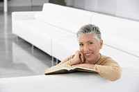 Woman with book on sofa smiling portrait (thumbnail)