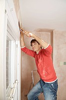 Man preparing wall of unrenovated room (thumbnail)