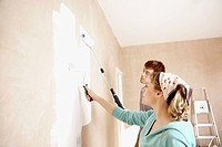 Couple painting wall with paint rollers indoors (thumbnail)