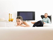 Woman on sofa and man in armchair in modern living room