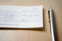 Cheque for one million dollars lying next to pen on table close_up