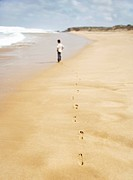 Boy walking along sandy beach back view