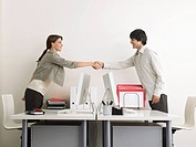 Man and Woman Shaking Hands over Desks side view