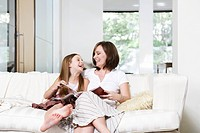 Mother and daughter reading book in living room portrait