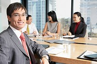 Business man sitting at boardroom table with colleagues portrait (thumbnail)