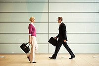Businesspeople Walking in Office Hallway side view