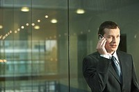 Businessman Using Cell Phone in front of window