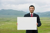 Smiling businessmen standing in mountain field holding blank sign front view