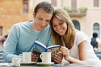Couple at outdoor cafe looking at guidebook of Rome front view
