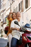 Middle_aged couple sightseeing on scooter in Rome Italy