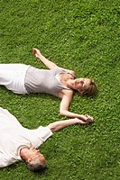 Middle_aged couple together sleeping on grass high angle view