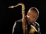 Pensive man holding saxophone looking down close-up (thumbnail)